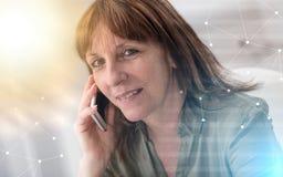 Mujer madura que invita al teléfono móvil, sobrepuesto con la red, efecto luminoso foto de archivo libre de regalías