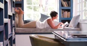 Mujer madura que miente en el libro de lectura del sofá en casa metrajes