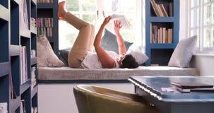 Mujer madura que miente en el libro de lectura del sofá en casa almacen de video