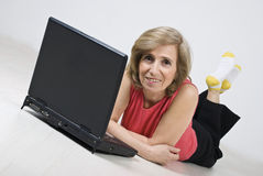Mujer madura que miente en suelo de madera usando la computadora portátil Imagen de archivo