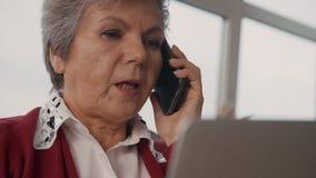 Mujer madura que mira la exhibición del ordenador portátil y que habla en celular almacen de metraje de vídeo