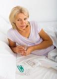 Mujer madura que pone en cama con las píldoras y el vidrio Imagen de archivo libre de regalías