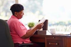 Mujer madura que pone la letra en la caja del recuerdo Imágenes de archivo libres de regalías