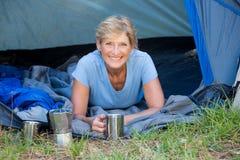 Mujer madura que pone la sonrisa y sostener una taza Fotografía de archivo