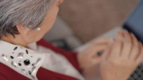 Mujer madura que pone los auriculares en sus oídos cuidadosamente almacen de metraje de vídeo