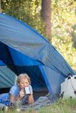 Mujer madura que pone y que bebe en una taza Foto de archivo libre de regalías