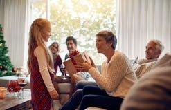 Mujer madura que recibe un regalo de la Navidad de su nieta fotos de archivo