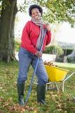 Mujer madura que recoge las hojas en jardín fotos de archivo libres de regalías
