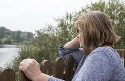 Mujer madura que se inclina en una cerca de madera Imagenes de archivo