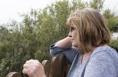 Mujer madura que se inclina en una cerca de madera Imagen de archivo libre de regalías