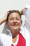 Mujer madura que se relaja en día asoleado imagen de archivo libre de regalías