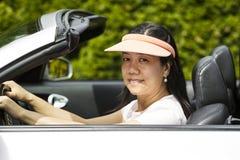 Mujer madura que se sienta en coche convertible en Niza día foto de archivo libre de regalías