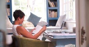 Mujer madura que se sienta en el libro de lectura del escritorio en Ministerio del Interior almacen de metraje de vídeo