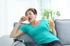 Mujer madura que se sienta en el sofá con la consola de la hamburguesa, de la soda y del videojuego imagenes de archivo