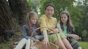Mujer madura que se sienta en la hierba debajo del ?rbol en el parque con dos nietas lindas Saque de la abuela almacen de video