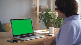 Mujer madura que se sienta en la tabla, mirando la pantalla del ordenador portátil en el interior casero almacen de metraje de vídeo