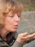 Mujer madura que sopla en la mano Fotografía de archivo