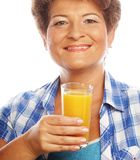 Mujer madura que sostiene un vidrio de zumo de naranja Foto de archivo
