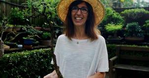 Mujer madura que sostiene una planta en el jardín 4k almacen de video