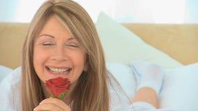 Mujer madura que sostiene una rosa almacen de metraje de vídeo