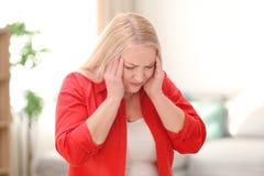 Mujer madura que sufre de dolor de cabeza Foto de archivo libre de regalías
