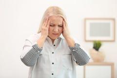 Mujer madura que sufre de dolor de cabeza Imagen de archivo