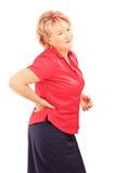 Mujer madura que sufre de un dolor de espalda Imágenes de archivo libres de regalías