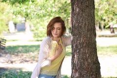 Mujer madura que tiene ataque del corazón cerca de árbol en parque verde imagen de archivo