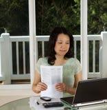 Mujer madura que trabaja en casa la oficina con las formas de impuesto Imagenes de archivo