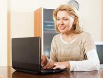 Mujer madura que usa el ordenador portátil en casa Imagen de archivo