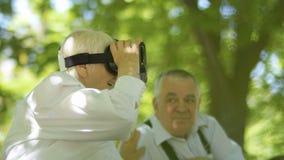 Mujer madura que usa los vidrios de la realidad virtual metrajes
