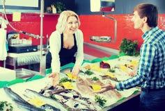 Mujer madura que vende pescados al varón imagen de archivo