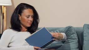 Mujer madura relajada que goza leyendo un libro en el sofá en casa metrajes