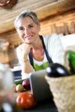 Mujer madura reservada que se coloca en cocina Fotografía de archivo libre de regalías