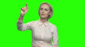 Mujer madura rubia que toca la pantalla imaginaria invisible