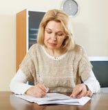 Mujer madura seria con los documentos financieros Fotos de archivo libres de regalías