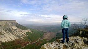 Mujer madura sola que se coloca en el borde del acantilado y de miradas en la visión Vestido en una chaqueta y vaqueros La visión Imagen de archivo libre de regalías