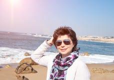 Mujer madura sonriente de 50 años en la playa imagenes de archivo