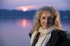 Mujer madura sonriente por el lago Foto de archivo libre de regalías
