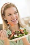 Mujer madura sonriente que come ensalada en casa Foto de archivo libre de regalías