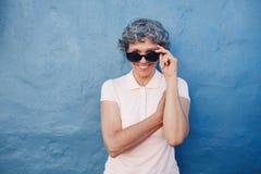 Mujer madura sonriente que mira a escondidas sobre las gafas de sol Fotos de archivo