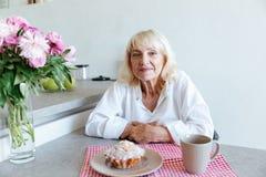 Mujer madura sonriente que se inclina en una tabla Fotografía de archivo libre de regalías