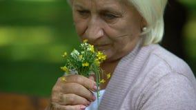 Mujer madura trastornada que mira el ramo de flores en sus brazos, memorias del campo metrajes