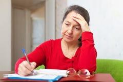 Mujer madura triste con las cuentas imagen de archivo libre de regalías