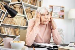 Mujer madura triste que agota del aprendizaje fotografía de archivo