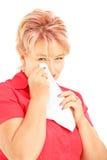 Mujer madura triste que limpia su ojo del griterío con el tejido Imagenes de archivo