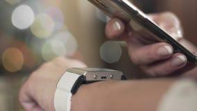Mujer madura usando el reloj elegante para explorar QR-código