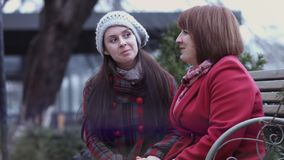 Mujer madura y su crecida hija que se sientan en un banco en el parque y la discusión de la ciudad Relación caliente ` S de la ma almacen de metraje de vídeo