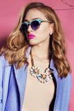 Mujer magnífica con el pelo rizado rubio en equipo de la primavera: capa, vestido y gafas de sol elegantes Imágenes de archivo libres de regalías