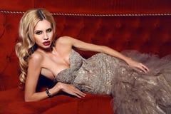 Mujer magnífica con el pelo rubio en el vestido elegante que miente en el diván rojo imagen de archivo